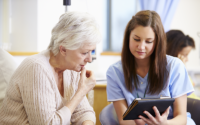 Woman and nurse sitting down and looking at an iPad.