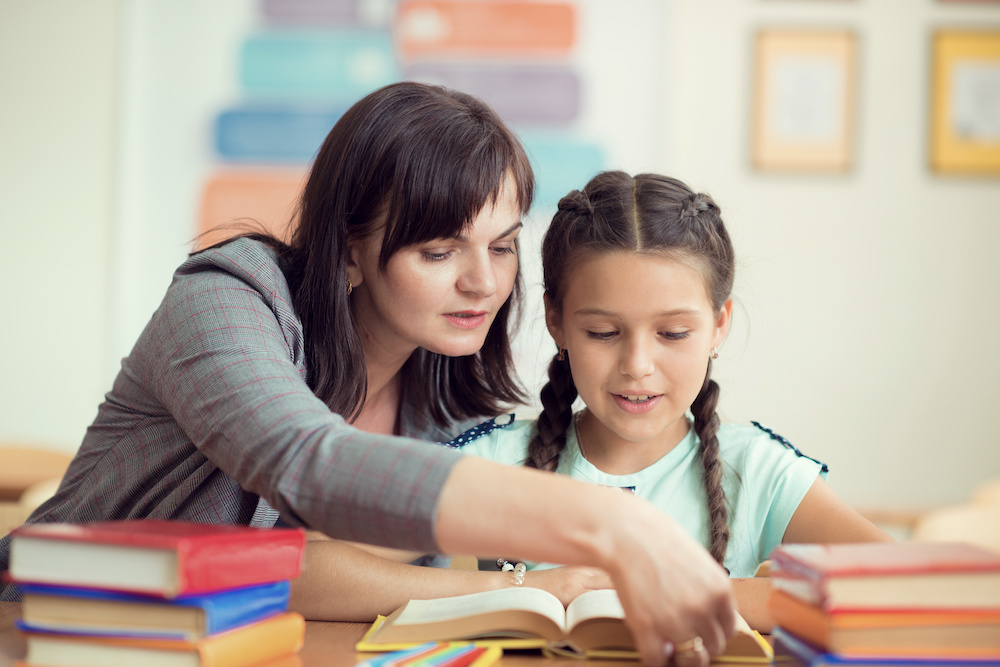 Photo of a lady supporting a young girl with reading